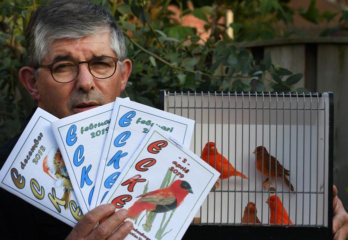 Voorzitter Henk van Valkenburg met een paar van zijn vogels en de laatste clubbladen.