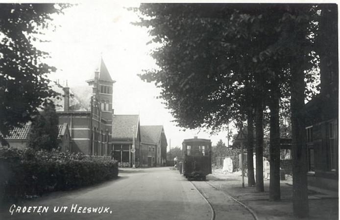 De tram in Heeswijk,  op wat nu de Hoofdstraat is. Aan de linkerkant de panden waarin nu Search en café De Zwaan zitten.