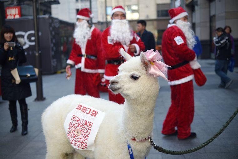 Kerstmannen maken reclame in een winkelcentrum in Peking. Beeld afp