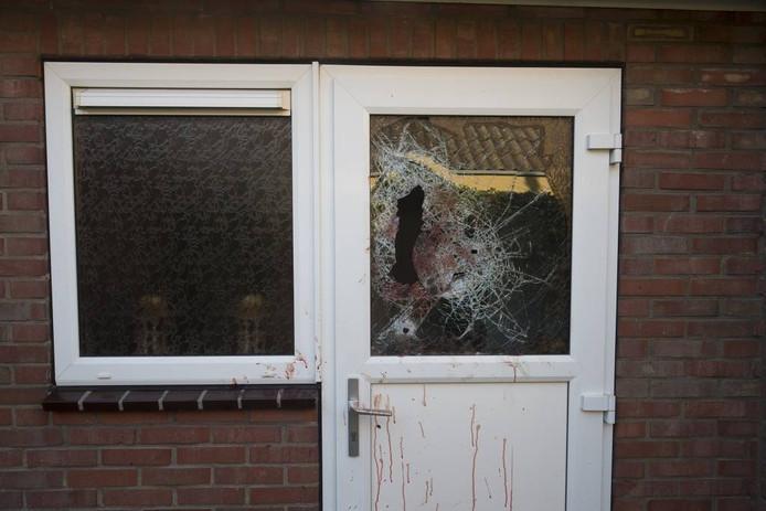 Een ingeslagen ruit en bloedsporen op de deur van de woning aan de Teubenweg in Keijenborg, waar de schietpartij plaatsvond.