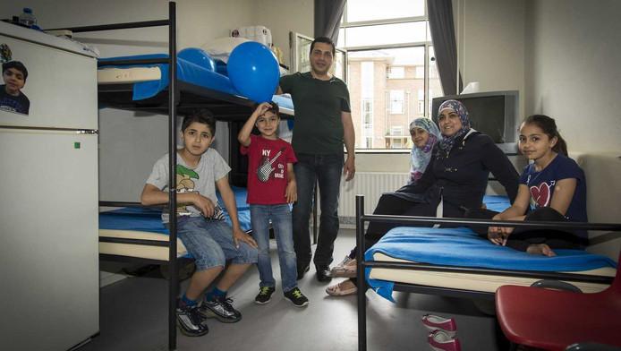 De familie Abrek met hun vier kinderen uit Syrie poseren op hun kamer in het asielzoekerscentrum in Utrecht