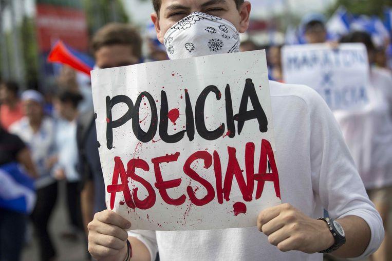 Demonstranten protesteren tegen de regering van Daniel Ortega in hoofdstad Managua.  Op het bordje staat 'politie moordenaar' ofwel 'de politie moordt'.