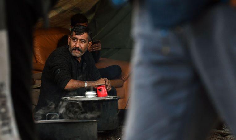 Een mgirant voor zijn tentje in het vluchtelingenkamp Vucjak.  Beeld AFP