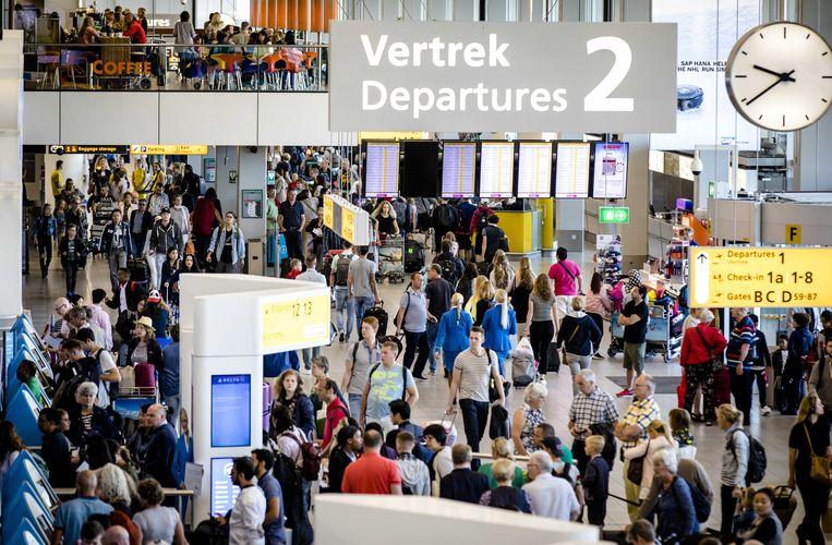Reizigers in de vertrekhal van Schiphol op 31 juli, de drukste dag van het jaar voor de luchthaven.