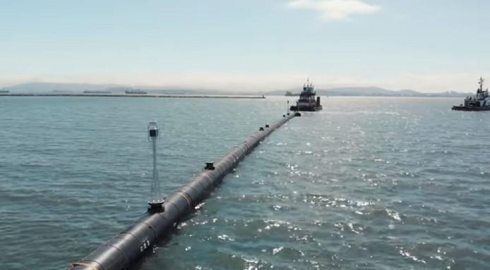 Een sleepboot trekt de 600 meter lange arm in de vorm van een C  de Baai van San Francisco uit naar de Grote Oceaan.