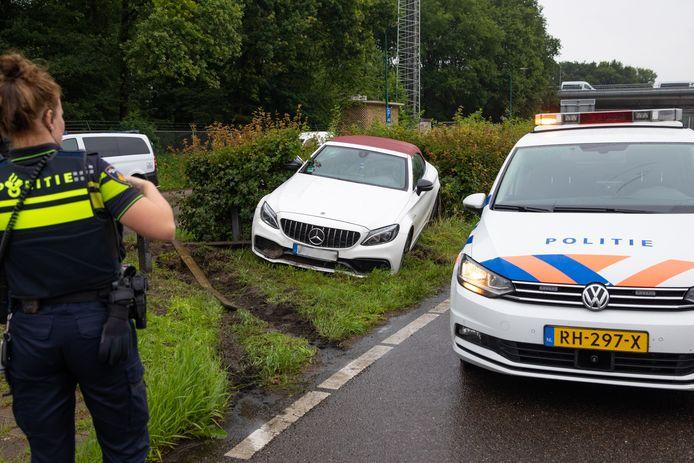 Een auto uit een rouwstoet raakte na het nemen van een rotonde in Baarn van de weg.