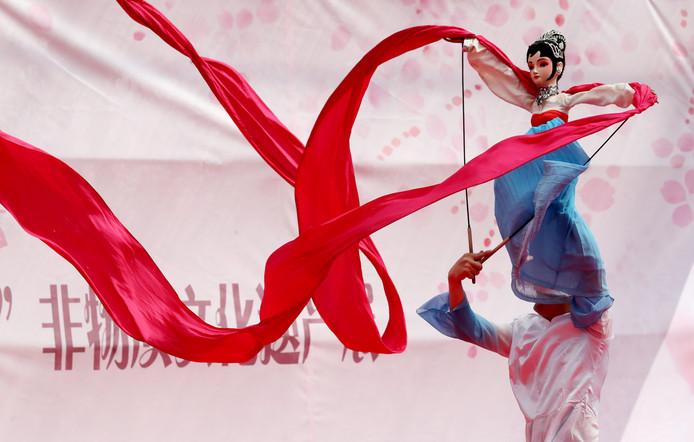 Een Chinese man geeft een voorstelling met zijn pop tijdens een cultureel festival in Kunming.