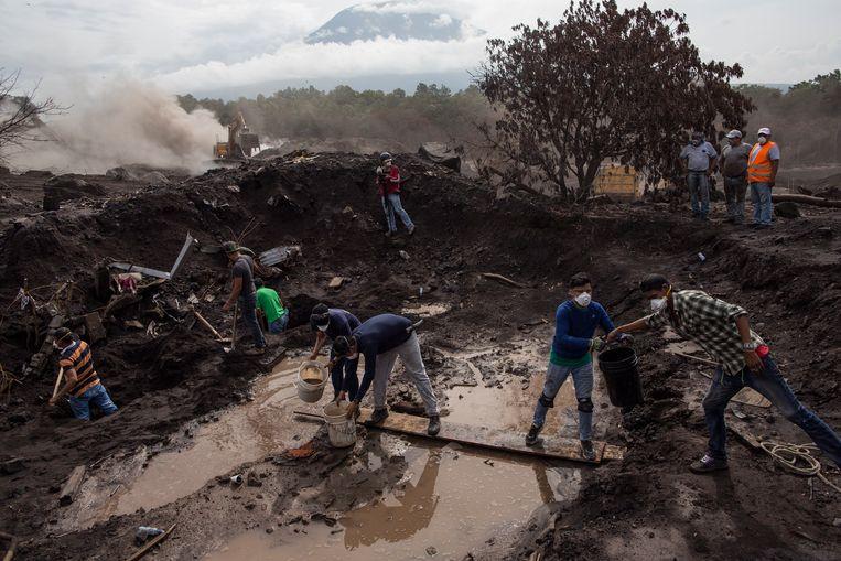 Familieleden en hulpverleners zoeken naar vermisten na uitbarsting van de Volcán de Fuego in juni 2018.