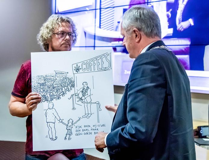 Erwin van der Worp (links) sprak onlangs namens omwonenden van de beoogde coffeeshop zijn ongenoegen uit in de Zwolse gemeenteraad. Hij had zelfs een kritische cartoon meegenomen voor de burgemeester.