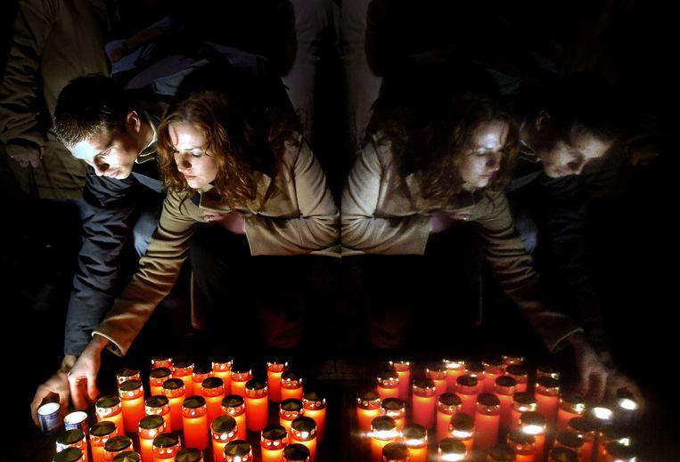 Mensen branden kaarsen tijdens de herdenking van de Kristallnacht bij het monument bij de stopera in Amsterdam. Beeld Joost van den Broek / de Volkskrant
