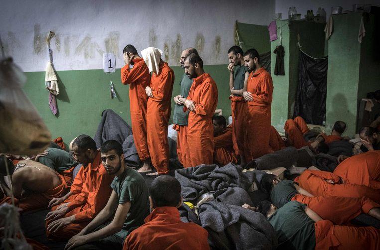 Opgepakte IS-strijders bidden in een Koerdische gevangenis in de Syrische stad Hasakeh, eind oktober. Beeld AFP