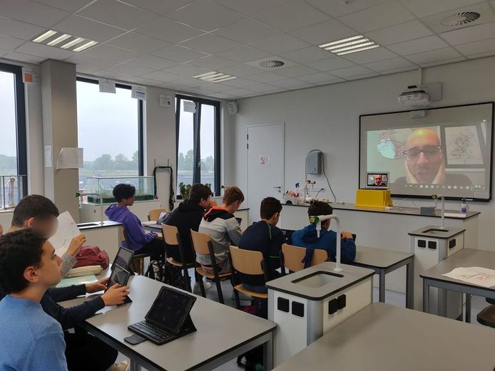 Een docent geeft vanuit huis via een videoverbinding les aan leerlingen van Rivers International School in Arnhem.