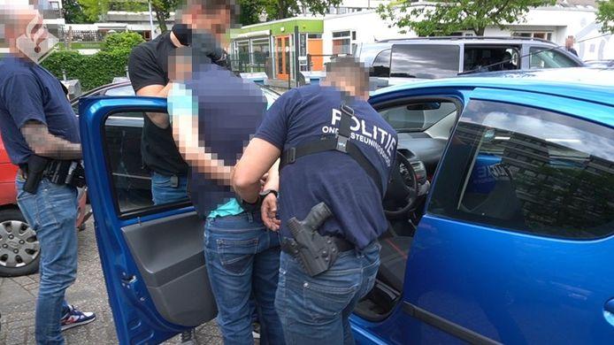 Een van de zes verdachten wordt door agenten geboeid afgevoerd naar het politiebureau.