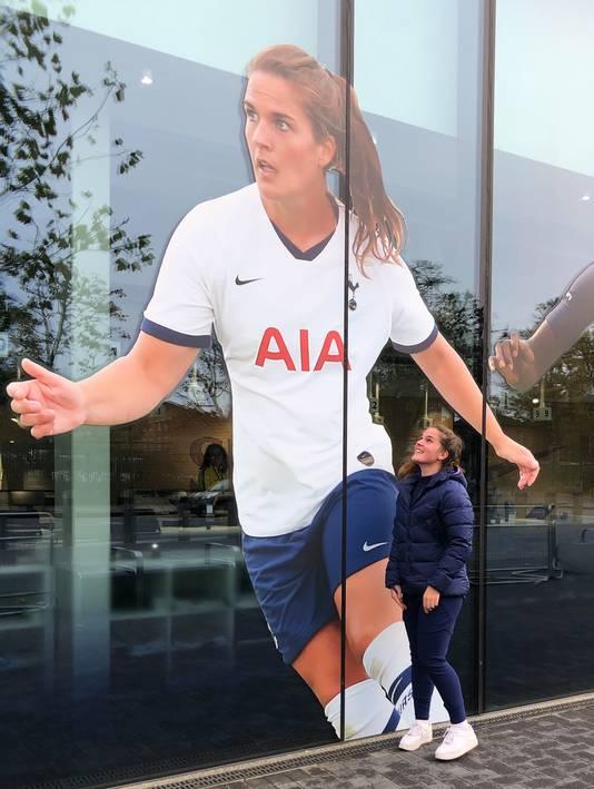 Siri Worm bij haar portret op een glazen gevel van het stadion.