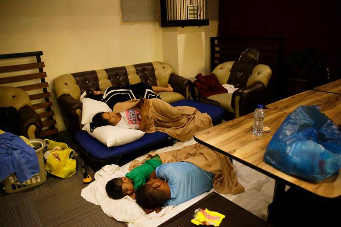 Inwoners uit de Filipijnse stad Tuguegaroa slapen in een hotel nadat hun huizen deels zijn vernietigd door de tyfoon Manghkut.