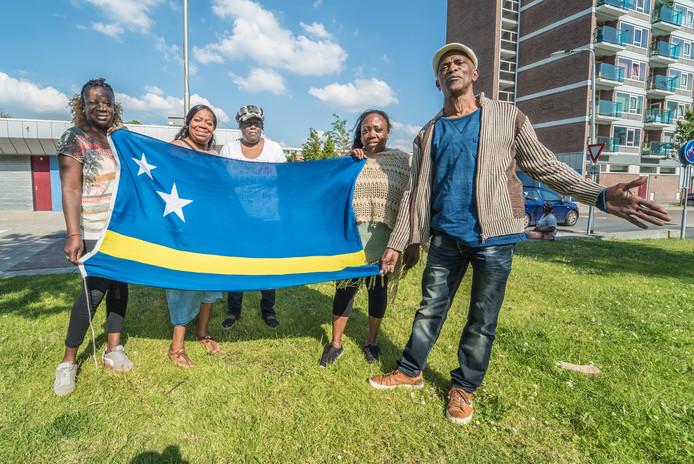 Monique en Mike Niles (rechts) tonen samen met enkele mede-organisatoren de vlag van Curaçao. ,,Een belangrijk symbool voor Antillianen.''