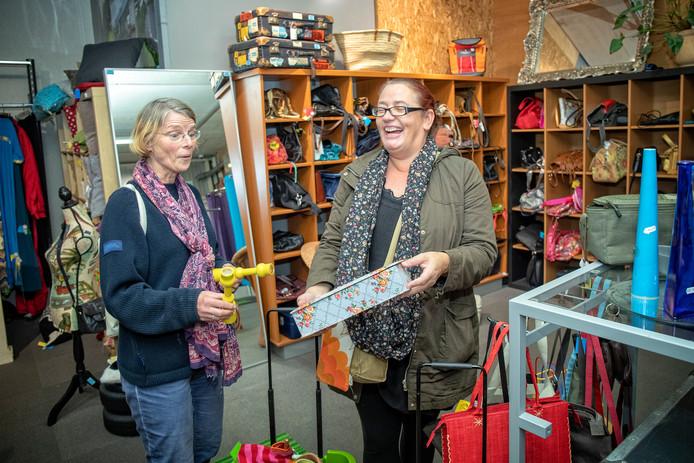 Kringloop-fanaten José van Hees (links, met twee kandelaars) en Ellen Kramer (met een mooi doosje) hebben het reuze naar hun zin in de kringloopwinkel van Alphen.