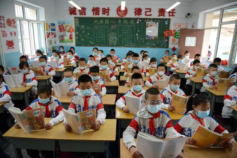 Leerlingen uit Binnen-Mongolië dragen mondkapjes in de klas. Beeld Getty