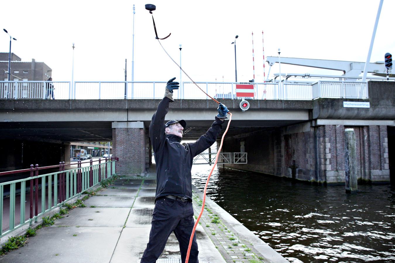 """Ron Hagen gooit met regelmaat  zijn touw met magneet in het water van de Schie:""""Je weet nooit wat er naar boven komt.''"""