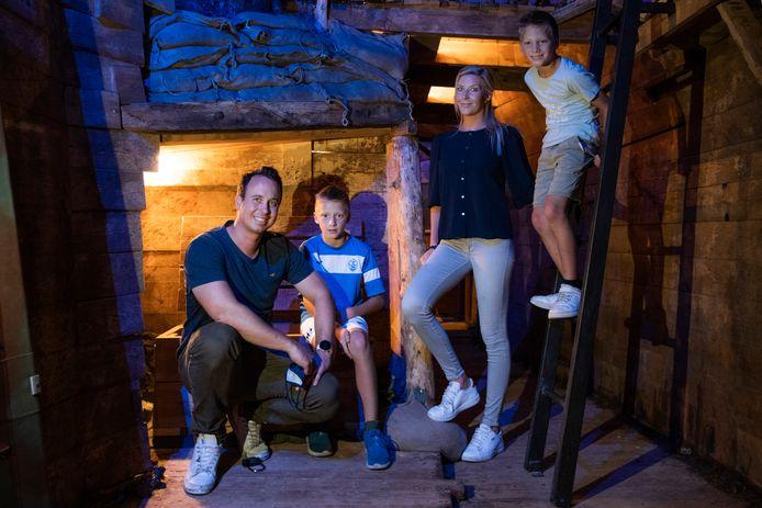 """Koen Van Breda en Annabel Coppens, samen met hun kinderen, in hun nieuwe escape room. """"Het is een serieuze uitdaging om hier in 60 minuten tijd uit de loopgraven te geraken"""", beloven ze."""