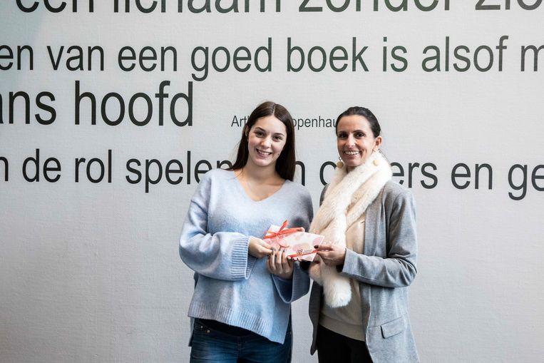 Elke Bruninx won met een gedicht over vrijheid de poëziewedstrijd van de bibliotheek in Tongeren. Schepen An Christiaens schenkt haar een boekenbon.