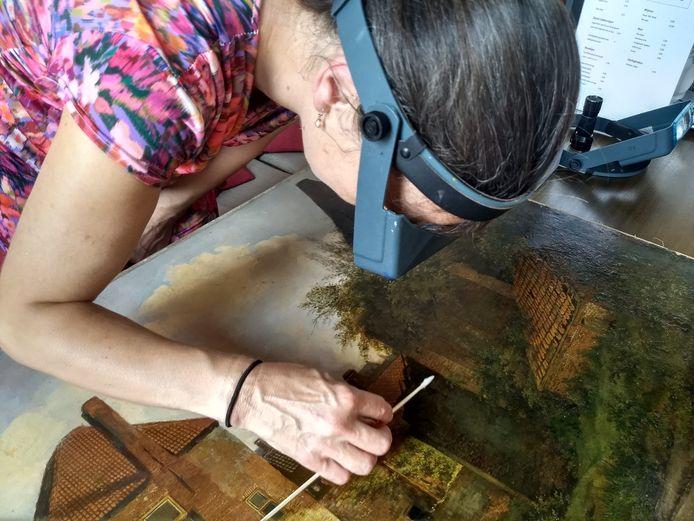 Restaurator Marieke Walison onderzoekt het schilderij Gezicht op de Rijnpoort te Rhenen uit circa 1838.