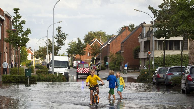 Kinderen in België spelen vandaag op straat na fikse regenbuien. Beeld belga