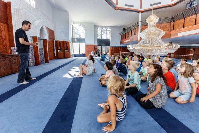 Kinderen luisteren geboeid naar de uitleg over de moskee in Roosendaal.