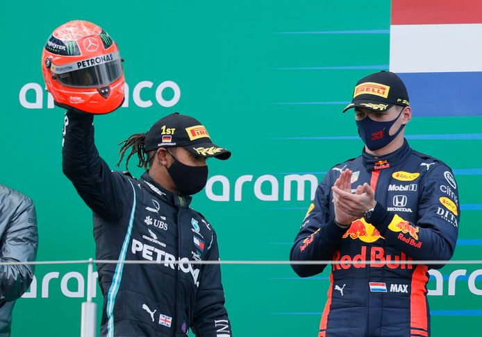Mercedes driver Lewis Hamilton of Britain holding the helmet of former F1 legend Michael Schumacher, celebrates after winning the Eifel Formula One Grand Prix at the Nuerburgring racetrack in Nuerburg, Germany, as Red Bull driver Max Verstappen of the Netherlands, right who finished second applauds him at the podium, Sunday, Oct. 11, 2020. Hamilton with this win equals 91 wins in F1 races as Michael Schumacher. Renault driver Daniel Ricciardo of Australia finished third. (Ronald Wittek, Pool via AP)