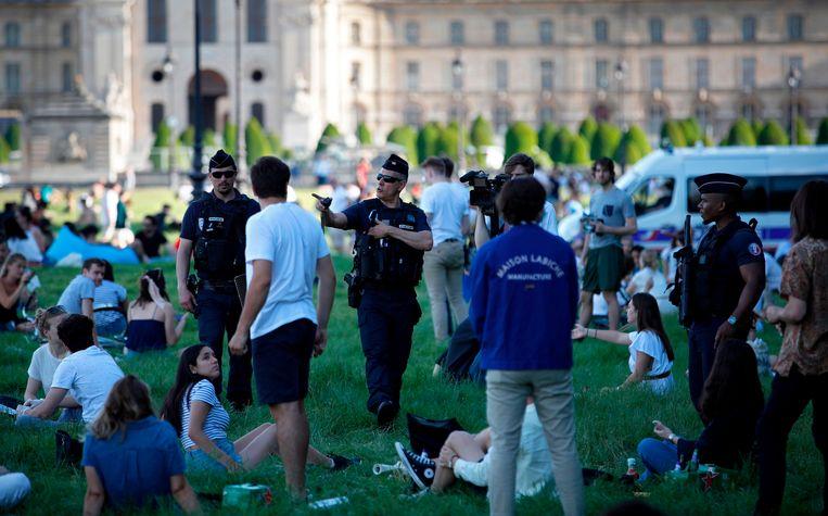 Agenten vragen bezoekers op het grasveld voor Hôtel National des Invalides in Parijs om afstand van elkaar te houden.  Beeld AFP