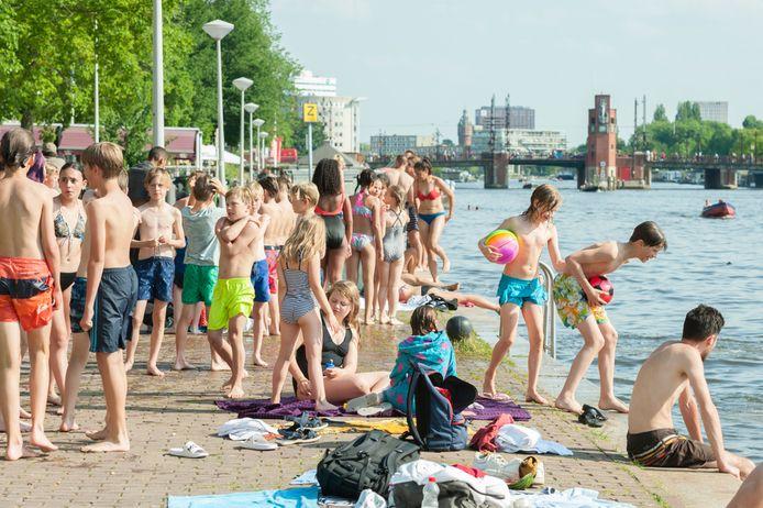 Kinderen zwemmen in het water in de Amstel in Amsterdam.