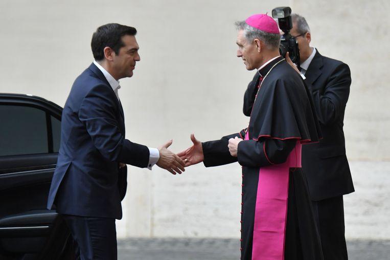 De Griekse premier Alexis Tsipras wordt verwelkomd door George Gänswein,  de prefect voor de Pauselijke Huishouding. Beeld ANP