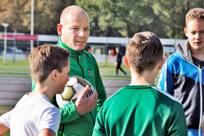 Clubheld Jurgen van de Groes tussen de jongeren op het voetbalveld bij AWC.