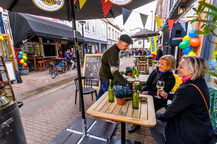 Oud-wethouder Gé Wagemakers serveert een drankje op het terras van zijn borrelcafé aan de Kerkstraat.
