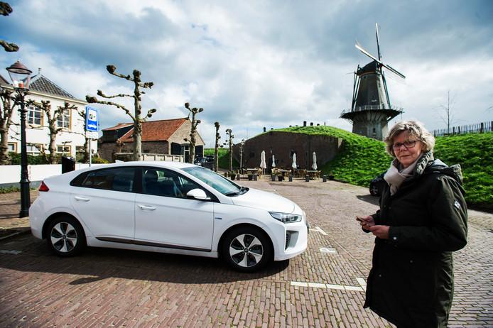 Lies Kersten bij de elektrische auto die ze deelt met 30 buurtbewoners in Woudrichem.
