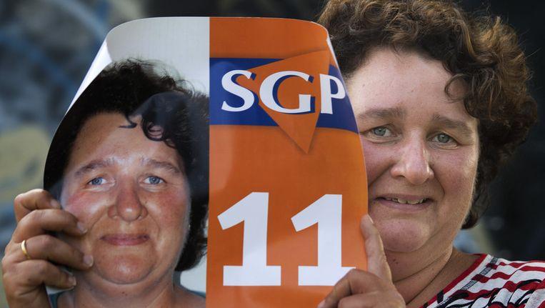 Lilian Janse houdt haar verkiezingsposter vast. Janse uit Vlissingen is de eerste vrouw die zich namens de SGP kandidaat heeft gesteld voor de verkiezingen. Beeld anp