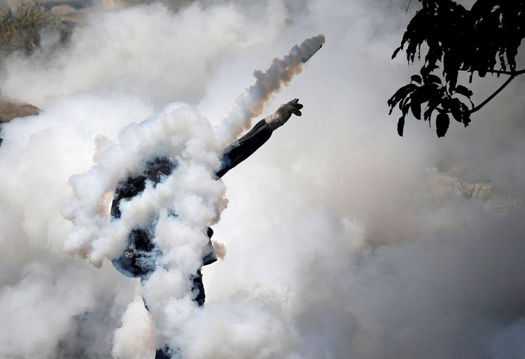 """A demonstrator throws back a tear gas grenade while clashing with riot police during the so-called """"mother of all marches"""" against Venezuela's President Nicolas Maduro in Caracas, Venezuela, April 19, 2017. Maduro said that beneath a peaceful facade, the protests were little more than opposition efforts to foment a coup to end socialism in Venezuela. The opposition said he has morphed into a dictator and accused his government of using armed civilians to spread violence and fear. REUTERS/Carlos Garcia Rawlins/File Photo  SEARCH """"POY VENEZUELA"""" FOR THIS STORY. SEARCH """"REUTERS POY"""" FOR ALL BEST OF 2017 PACKAGES.  TPX IMAGES OF THE DAY."""