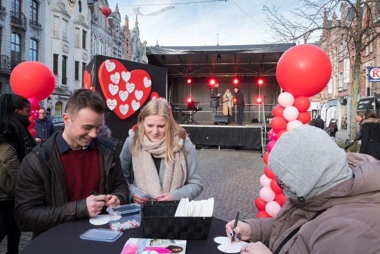 Een jongen en een meisje delen hun liefdesboodschap op de IJzerenleen.
