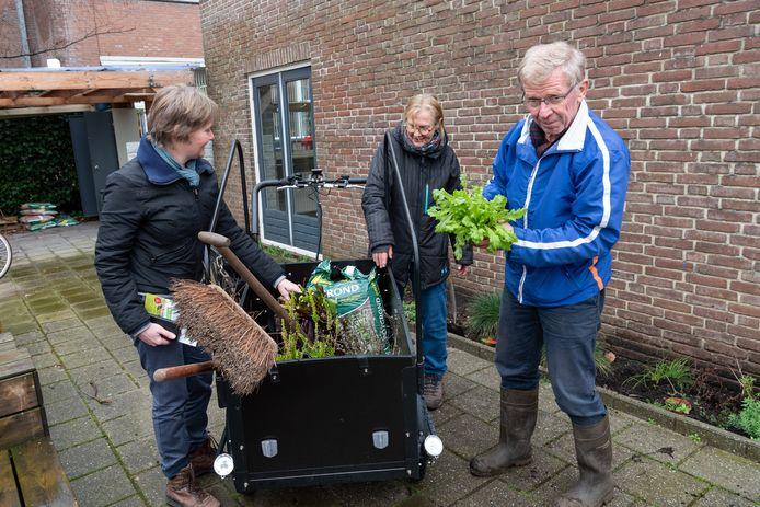 Plantjes uit de logeertuin gaan in de bakfiets, op weg naar een nieuwe tuin. Vlnr: Marieke, Joke en Jacque.