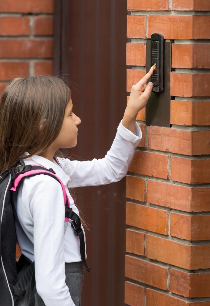 Een meisje belt aan bij de deur.