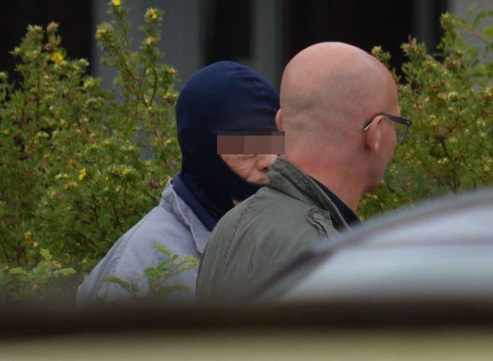 Beschuldigde Mohamed Koukouh (met muts) tijdens de reconstructie.