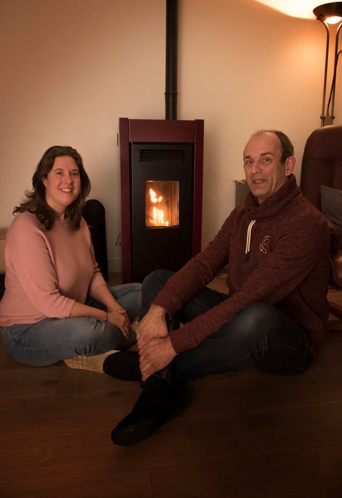 Tanja van den Bosch en Erik Siemens bij hun haard in de woonkamer. ,,De pelletkachel geeft heerlijke stralingswarmte, hij is deels betaald met subsidie.''