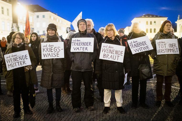 Een groepje demonstranten bij de ceremonie in München.  Beeld Matthias Balk / DPA