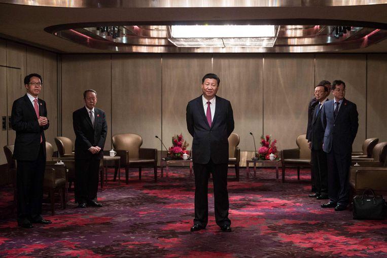 China's president Xi Jinping (midden) wacht in een hotel in Hongkong op Leung Chun-ying, de leider van de stadsstaat. Het was deze week zijn eerste bezoek als president. Beeld AFP