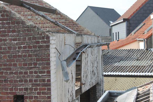 De dakgoot bengelt aan de verloederde woning