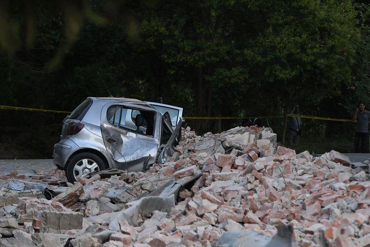 Het dak van een gebouw stortte door de aardbeving in en kwam neer op een auto terecht gekomen. Beeld AFP