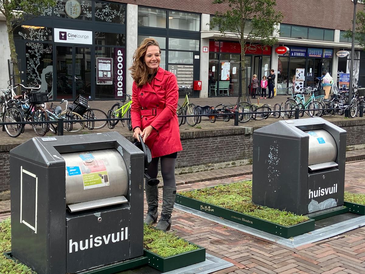 Wethouder Hilde de Groot geeft de tuintjes water die sinds deze week afvalcontainers omringen in Houten.