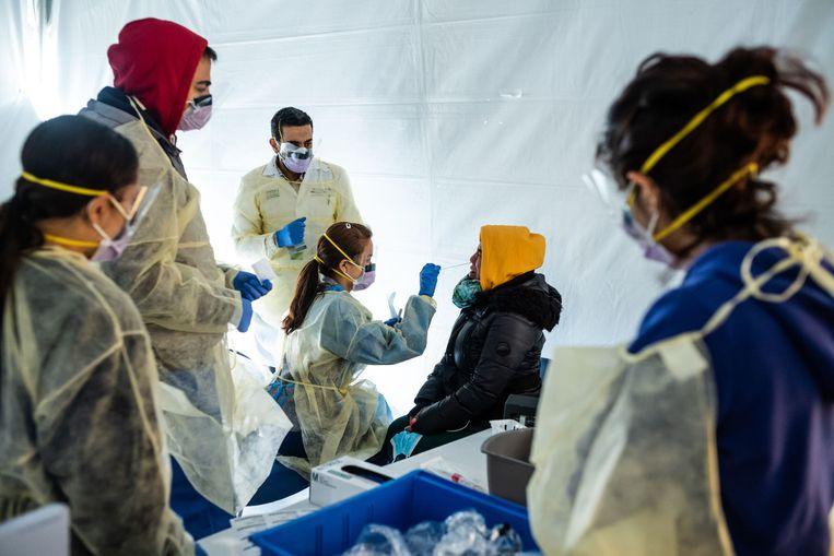 Zorgmedewerkers worden getest op het coronavirus voordat ze naar binnen mogen in het St. Barnabas Hospital in New York. Beeld AFP