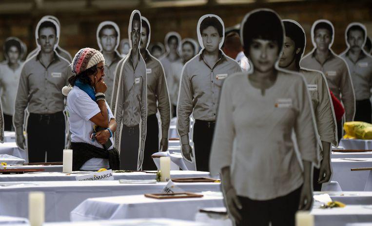 Een vrouw op het Bolivarplein in Bogotá loopt tussen afbeeldingen op waar formaat van vermisten van de Patriotic Union, de partij die was gelieerd aan de Farc. Beeld AFP