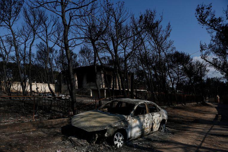 Een uitgebrande auto in het gebied waar de branden woedden. Beeld EPA